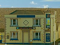 Chesil Bank looms over a pub in Chiswell