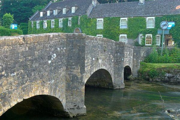 Bridge Over The River Coln With Famous Bibury Landmark Of Swan Hotel In