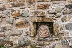 A skep, or traditional wicker beehive set into the garden wall