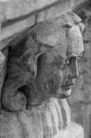 Carved head on font