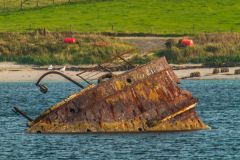A rusted blocking ship sunk offshore