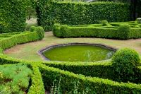 Formal gardens with clipped hedges and a pool