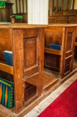 A sliding apprentice seat on a pew