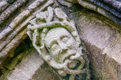 Green man carving on church tower
