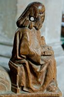 Seated figure arm-rest carving