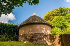 A stone and thatch roundhouse in the garden