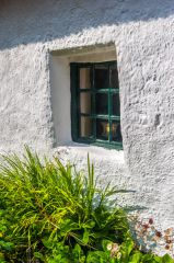 An old window in the whitewashed cottage wall