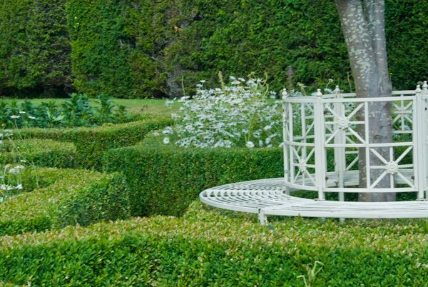 Herstmonceux Castle photo, Clipped hedges and a garden bench