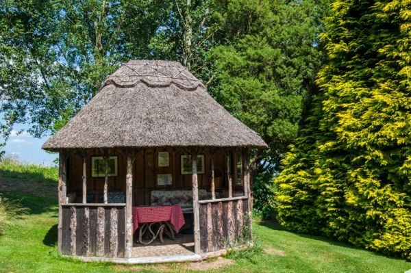 Little Malvern Court photo, A thatched summer house in the garden