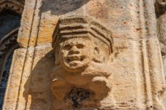 Carved head on the south exterior wall