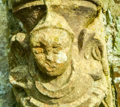 Carved head in the churchyard