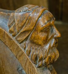Man's head on a choir stall