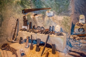 Historic tool display near the cave entrance