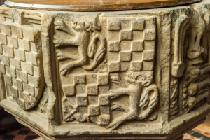 Intricately carved coat of arms on the font