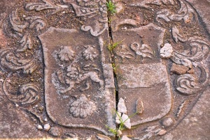 A worn coat of arms on a grave slab