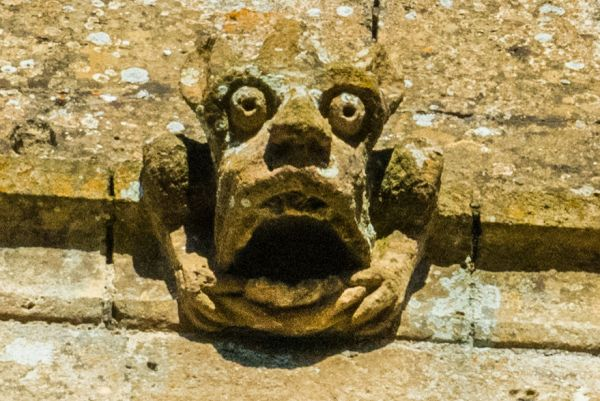 Compton Abdale, St Oswald photo, Grotesque carved head on the tower west face