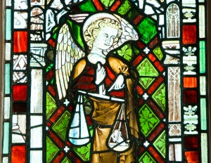 Stained glass figure of St Michael weighing souls