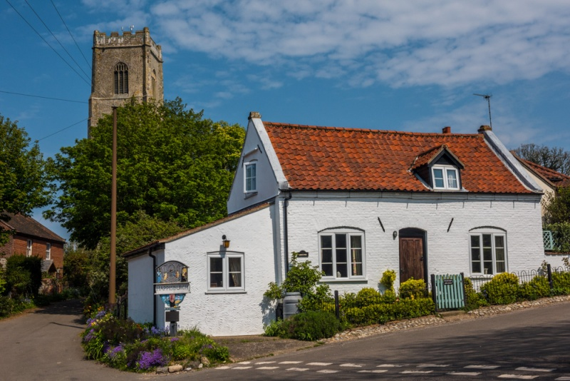 A whitewashed cottage and church tower in Happisburgh