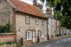 A row of traditional brick and stone cottages on Burnham Road