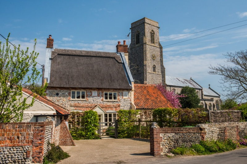 A thatched cottage and St Botolph's Church, Trunch