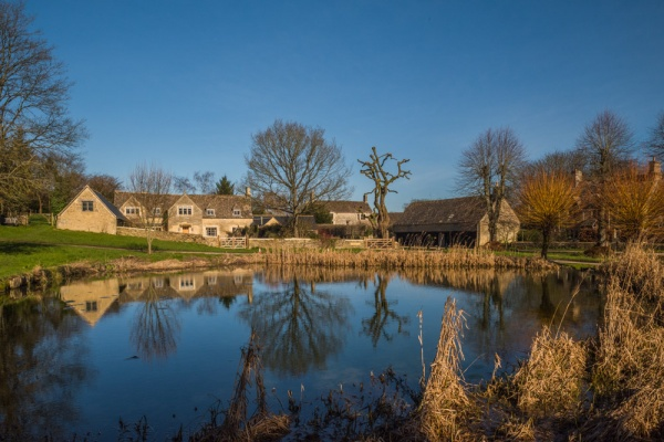 Westwell village pond and Cotswold stone cottages