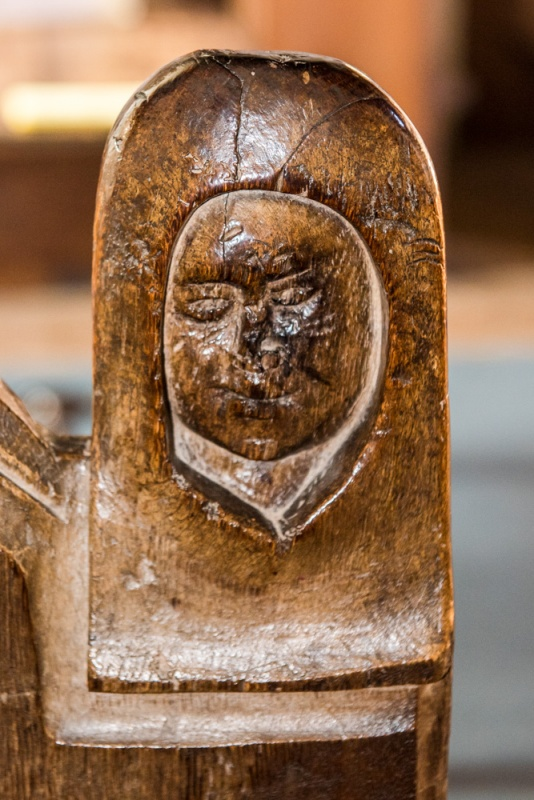 15th century bench end carving of a woman