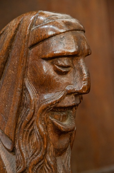 Carved head bench end on a choir stall